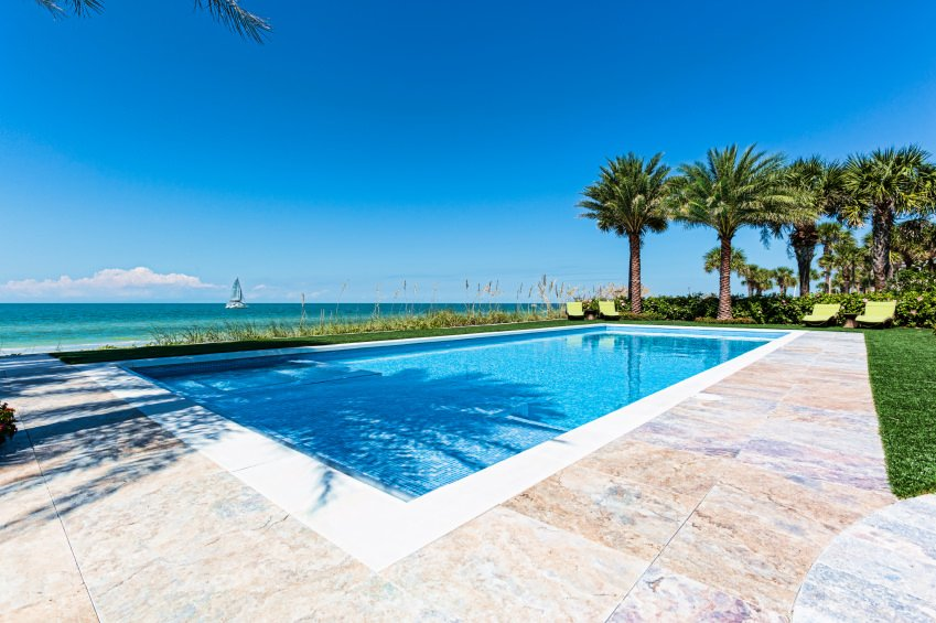 A rectangular swimming pool with white surround tiles and stone deck. You can sense a tropical feel in this place along with a magnificent ocean view.