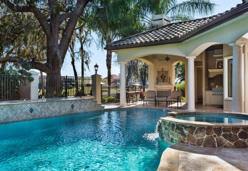 This patio is framed with white columns offering comfy seats that face the sparkling swimming pool embedded with a hot tub.