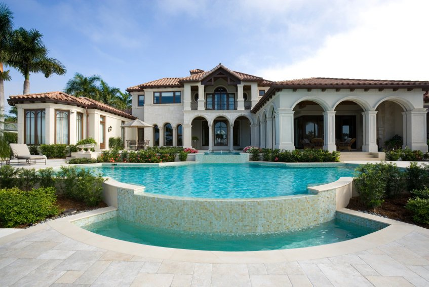This house features a patio framed with open archways and a resort-like swimming pool accented with lovely plants.