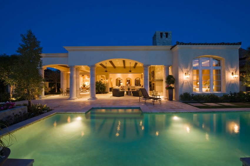 This house showcases a spacious patio framed with columns along with a luminous swimming pool that sparkles at night.
