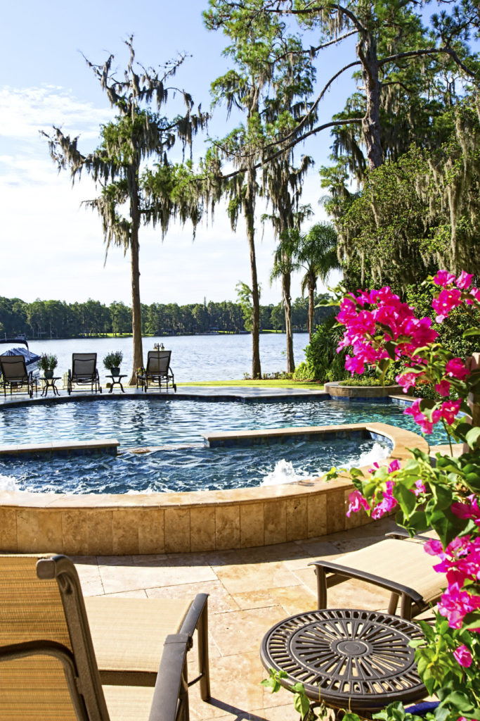 A curved swimming pool with a semi-circular jacuzzi and wicker lounge chairs facing the stunning river that's lined with tall trees.