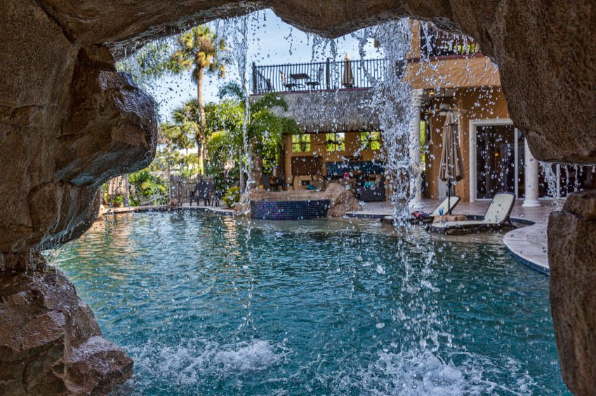 A view through the waterfall feature at this swimming pool with lounge chairs on the side next to the hot tub that's surrounded with rocks.