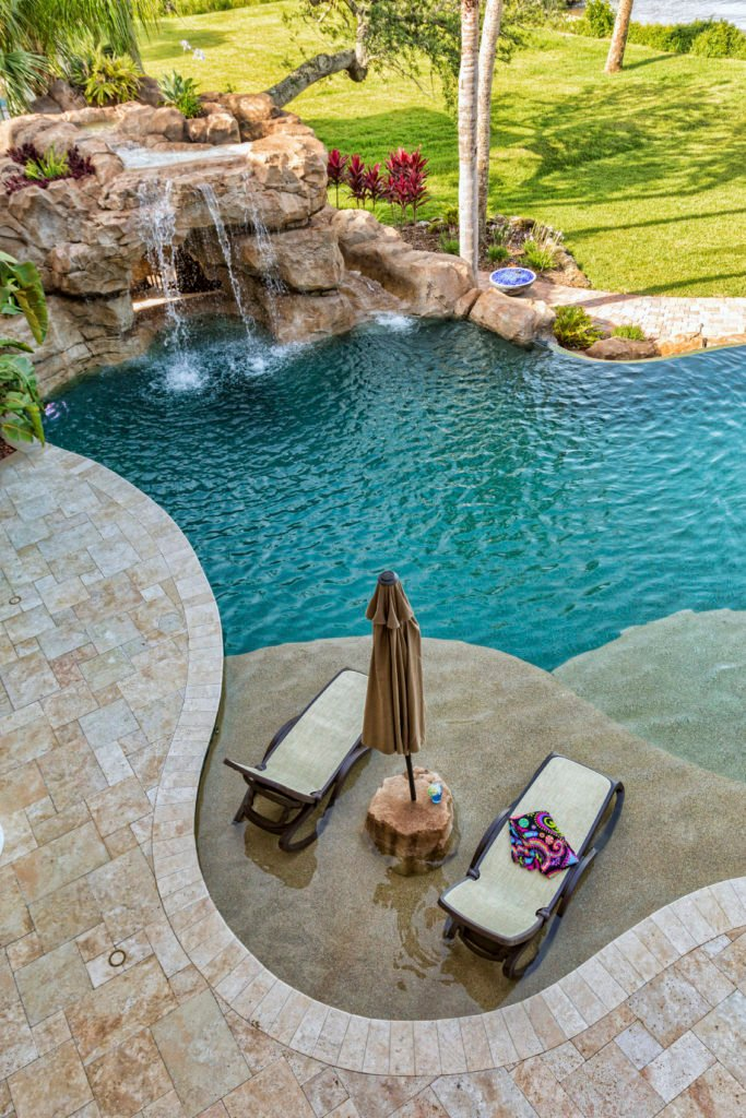 A backyard pool accented with rock waterfall and slide. It goes well with the greenery with that feeling of being close to nature.