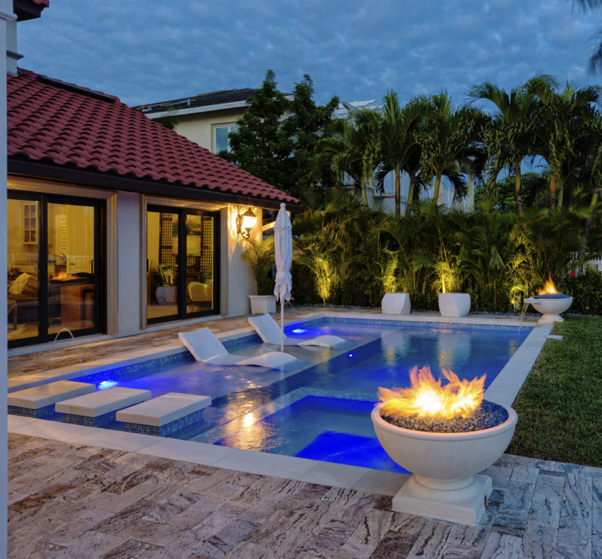 This house features a lovely swimming pool with fire bowls and concrete pathway going to the spa. It includes matching lounge chairs sitting inside the pool.