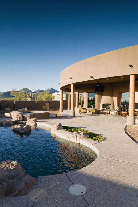 Southwestern house showcases a freeform swimming pool with concrete pavers and a hot tub accented with large rocks. There's a seating area in the patio offering a kiva fireplace.