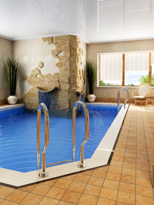 A charming indoor pool boasts a water feature that's fixed to the beige walls. There's a wooden round back chair by the glass paneled windows covered in striped roman shades.