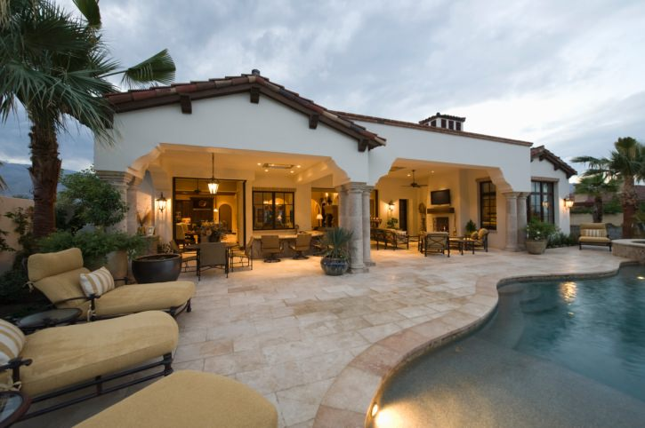 Mediterranean house with a patio that offers multiple seats and tables. It features a freeform swimming pool with comfy lounge chairs over brick paver.
