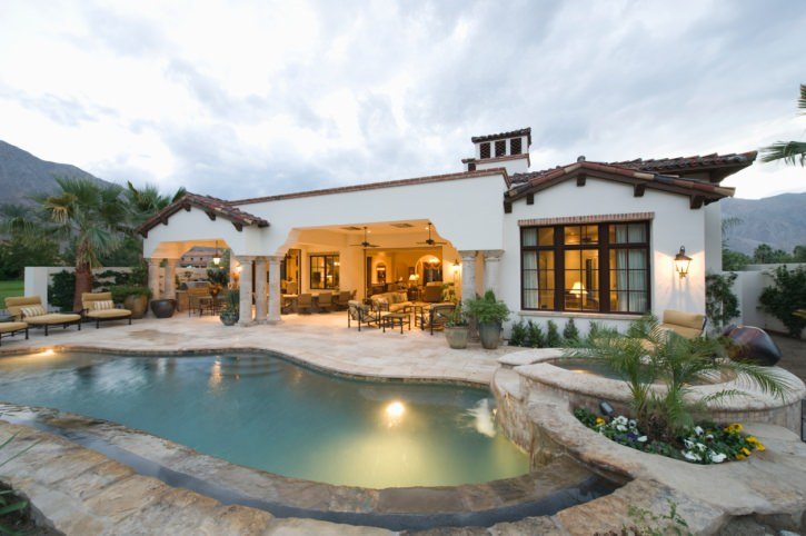 This house boasts a freeform swimming pool with a jacuzzi that's topped with a jar water feature. It offers beige loungers accented with striped pillows.