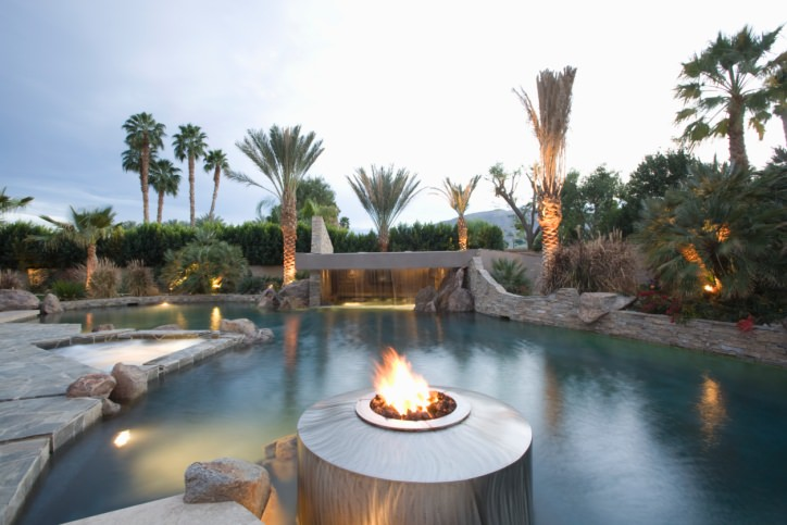A marvelous stone swimming pool boasts a jacuzzi along with a fire pit and gorgeous waterfall feature that's accented with palm trees.