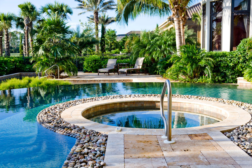 A jacuzzi sporting a keyhole design surrounded by pebbles and situated inside the magnificent infinity pool.