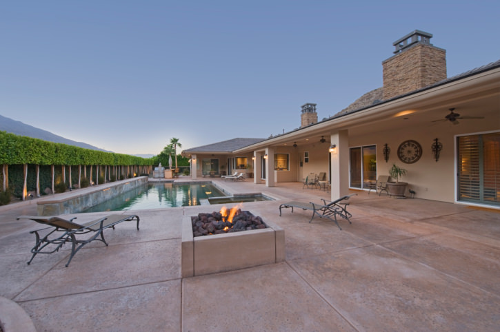 This home showcases a swimming pool lined with beautiful hedge plants and accompanied with a fire pit and wooden lounge chairs.