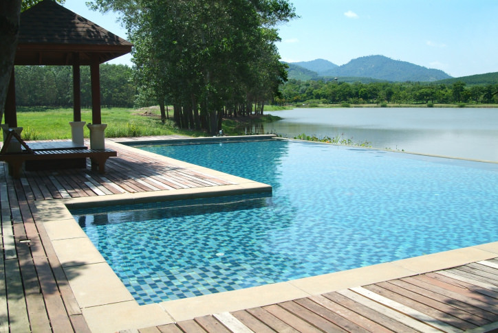 An L-shaped infinity pool overlooking a magnificent mountain view showcases a gazebo and wooden lounge chair that sit on wood plank deck.