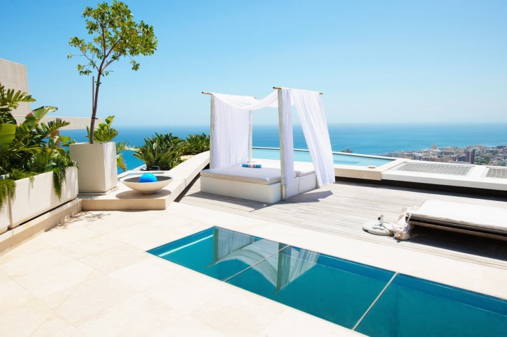 A sleek swimming pool with a serene ocean view features a white cabana bed that sits on a wooden deck.