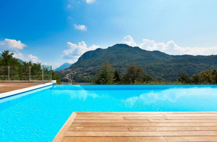 A stunning infinity pool overlooking an amazing mountain view showcases wooden decks framed with glass railings.