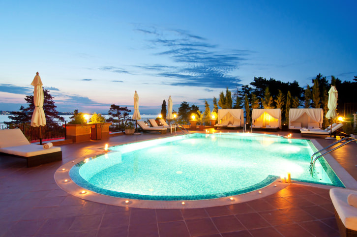 A luminous swimming pool surrounded with wrought iron fence along with white lounge chairs and cabana tents.