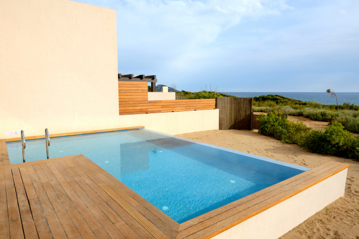 An L-shaped swimming pool on the sand and near the ocean showcases stainless steel handrails and wood plank deck.