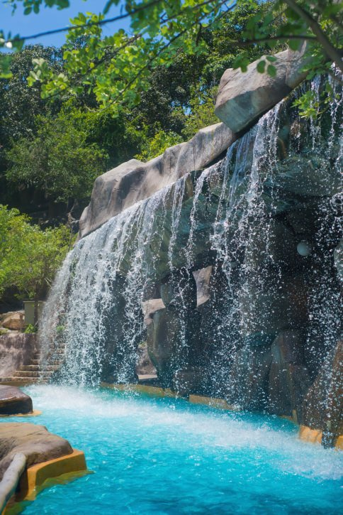 A gorgeous swimming pool accented with a magnificent waterfall. You can feel the cool ambiance brought by the plants and trees.