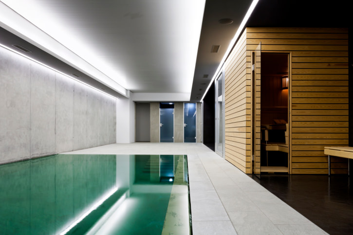 A sleek indoor pool fixed to the concrete paneled walls that match with the brick flooring. It is aligned with the tray ceiling fitted with strip lighting.