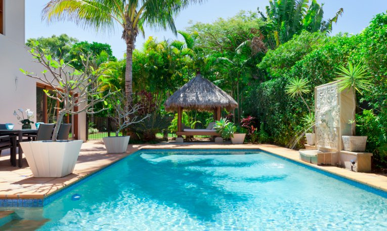 The sparkling swimming pool boasts a waterfall feature accented with lovely plants and a tiki hut topped with white cushion and fluffy pillows.