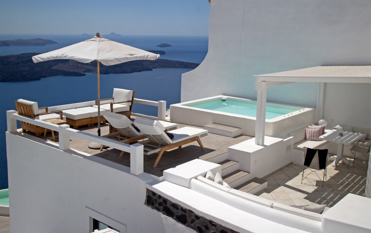 Swimming pool with a breathtaking scenic view offers white lounge chairs and a cabana next to it with comfy built-in seats.