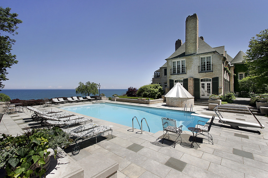This mansion offers an in-ground pool overlooking the ocean. It is lined with patterned loungers and matching chairs over brick pavers.