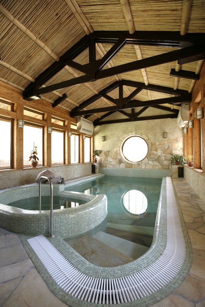 A cozy swimming pool with a hot tub attached to it. It is enclosed with glass paneled windows and cathedral ceiling with exposed wood beams.