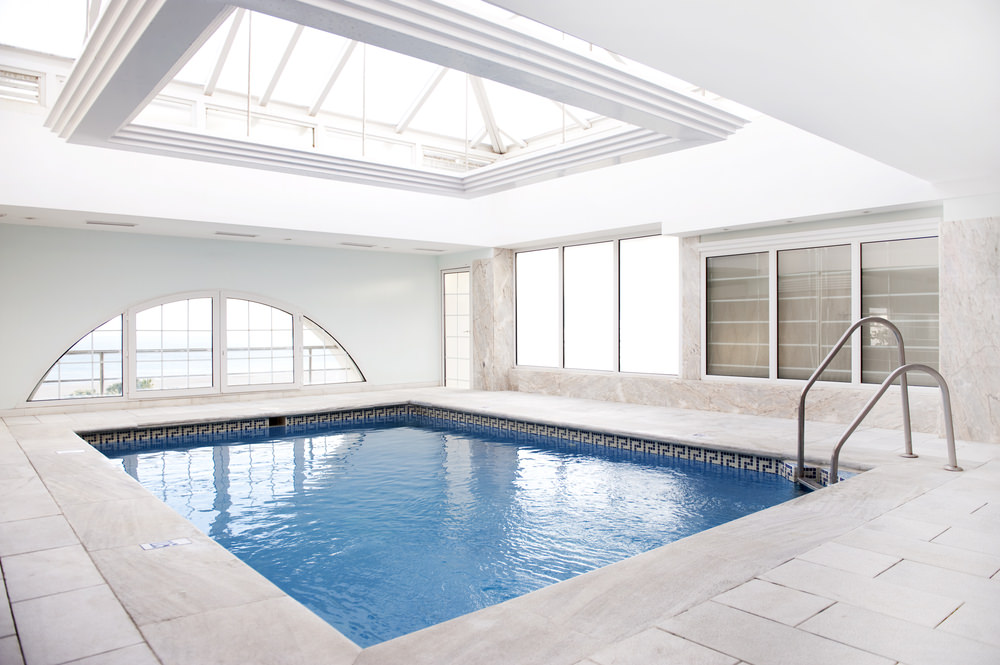 A bright indoor pool with concrete tiled pavers and glazed windows and ceiling that bring plenty of natural light in.