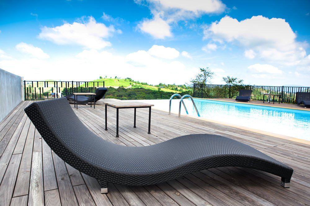 An in-ground swimming pool enclosed in black metal railings offers stylish lounge chairs and natural wood tables that complement with the wood plank decks.