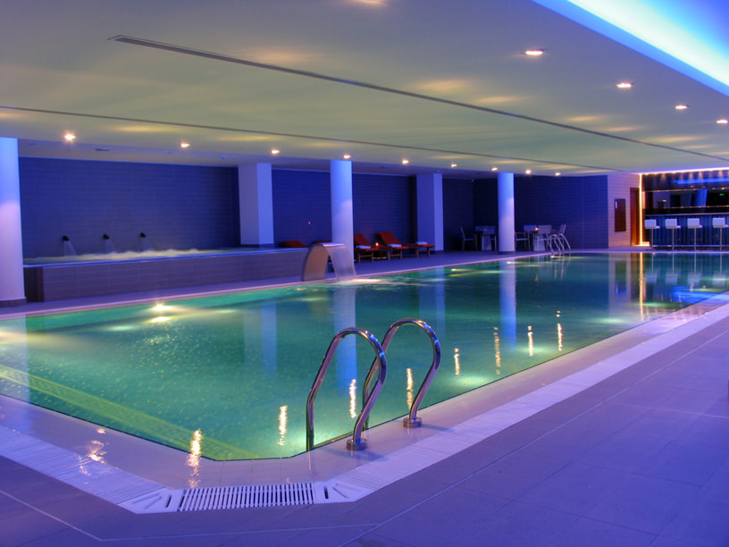 A magnificent indoor pool with a bar accompanied by a raised spa along with red loungers and white seating area in the corner.