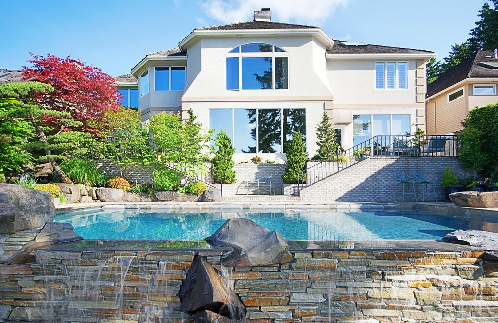 Luxury house with glazed windows and brick outdoor staircases leading to this swimming pool that's accented with a stone brick waterfall feature.