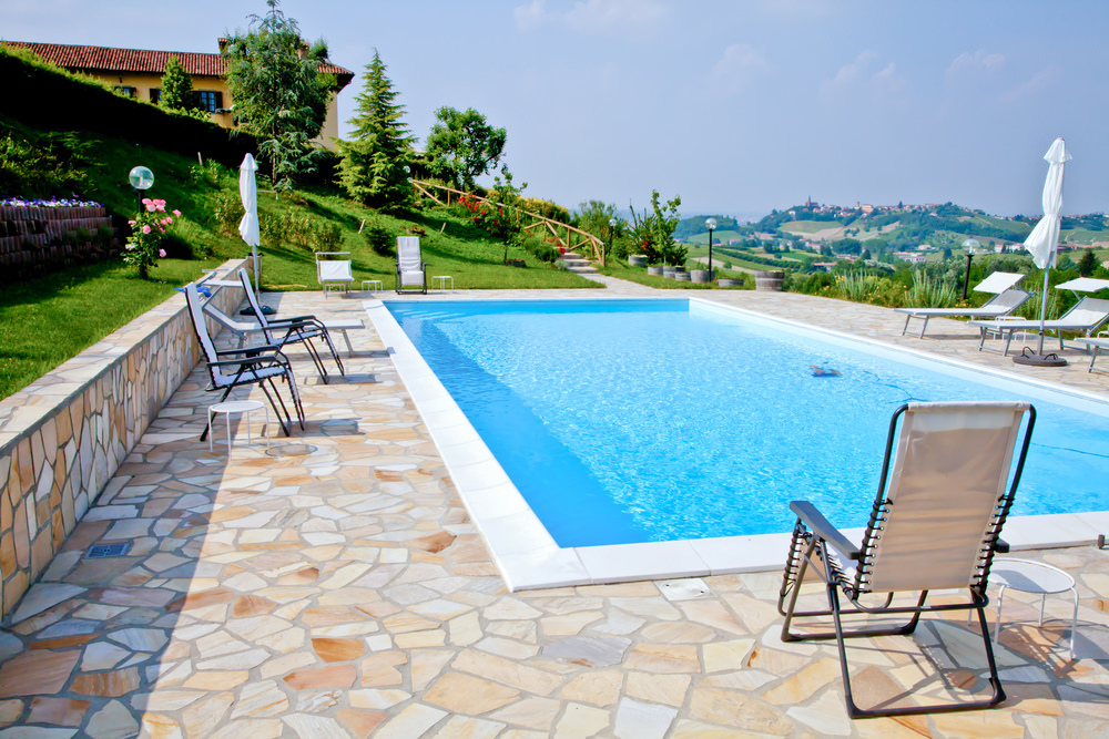 A rectangular swimming pool overlooking a beautiful outdoor scenery with white lounge chairs and flagstone pavers and wall.