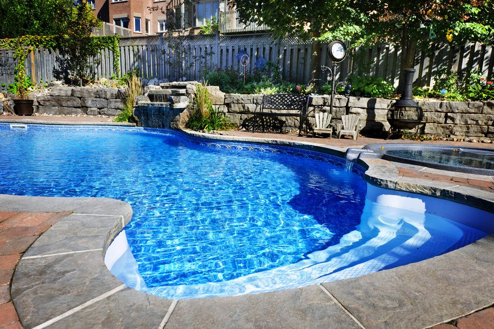 A bright blue swimming pool with a jacuzzi and waterfall feature fixed to the stone retaining wall. It also offers a freestanding fireplace next to the black bench and wooden chairs.