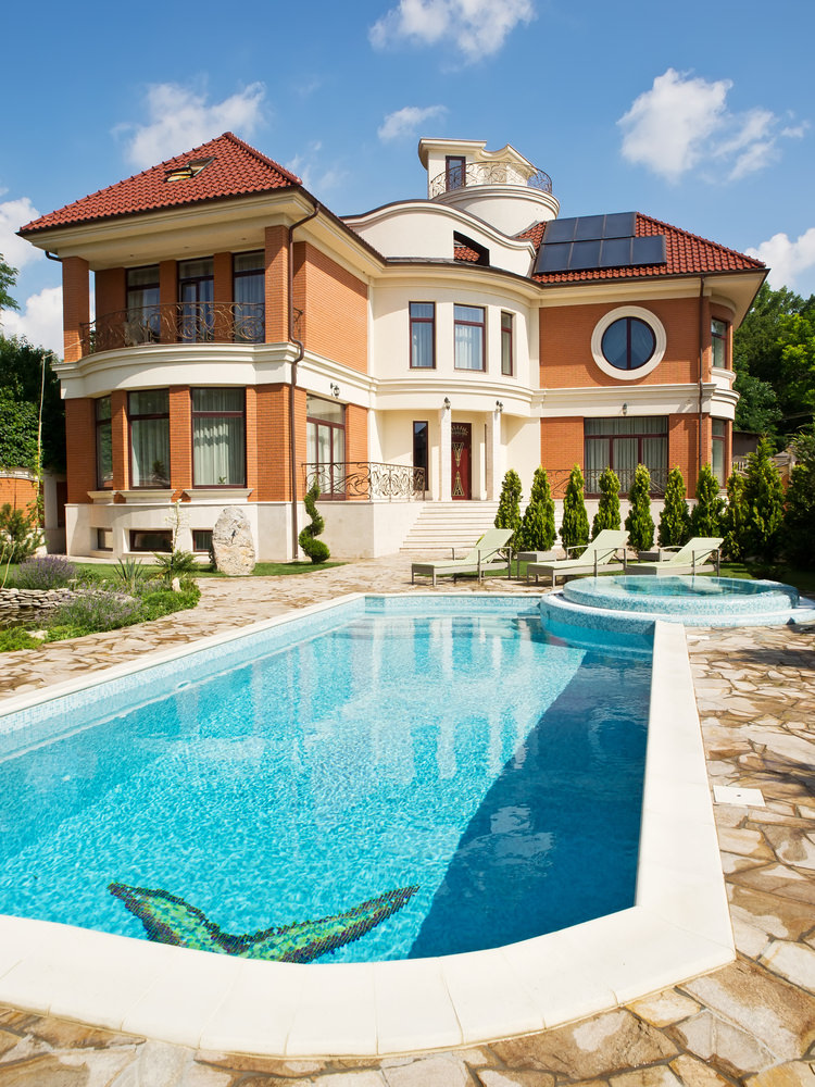 A sophisticated house showcases an in-ground swimming pool with a hot tub clad in blue mosaic tiles. It has beige lounge chairs that sit in front of the lovely pine trees.