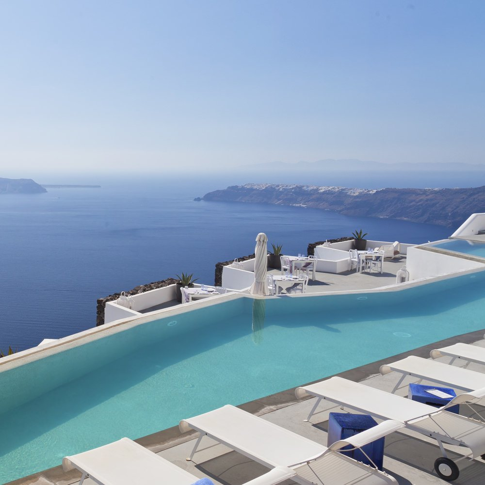 A luxurious swimming pool lined with mobile loungers and blue cube side tables. It offers multiple seats in front overlooking a stunning ocean view.