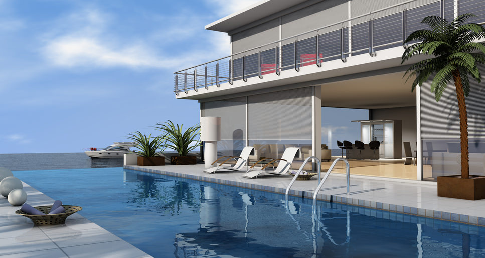 Contemporary house features a luxury infinity pool with sleek lounge chairs and round decors. With its infinity design, it may appear like it's connected to the ocean.
