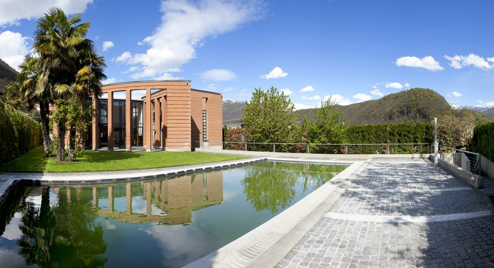 A modern house with full height glazing and lush green lawn next to the in-ground swimming pool with concrete pavers that are framed with metal fences.