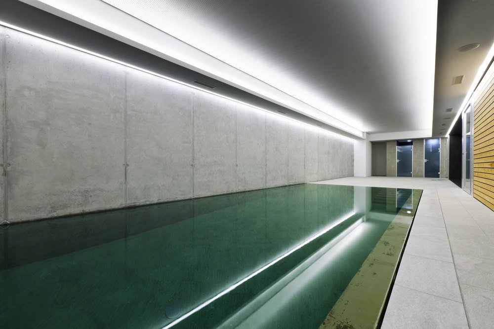 Large indoor swimming pool surrounded by gray walls and a classy tray ceiling.
