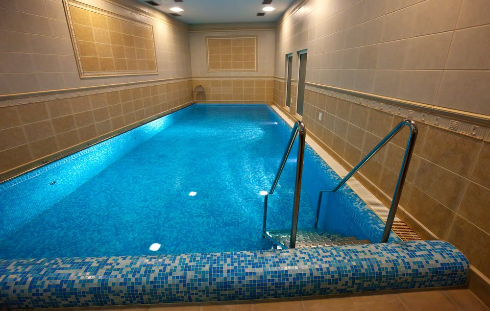 This beige tiled room is filled with a swimming pool that's taking up the whole space to itself. It is clad in blue mosaic tiles and includes a stainless steel ladder.