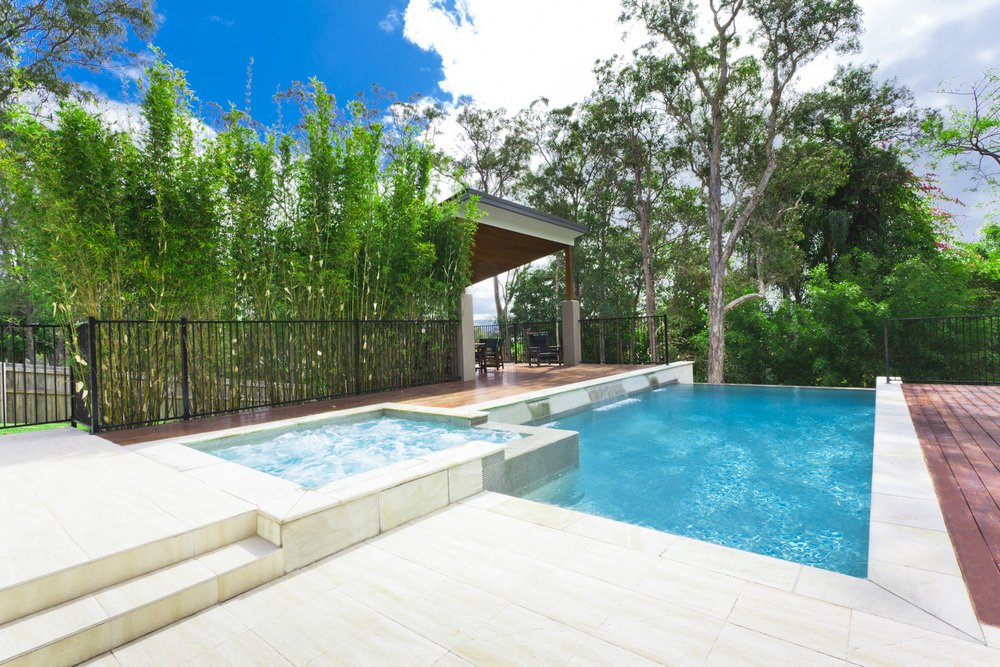 A tranquil swimming pool in between wood plank decks boasting waterfall feature and a jacuzzi. It includes a cabana on the side with cozy seats framed with wrought iron railings.