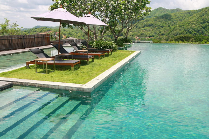A relaxing seating area featuring black loungers with wooden side tables and umbrellas situated in the middle of this stunning infinity pool.