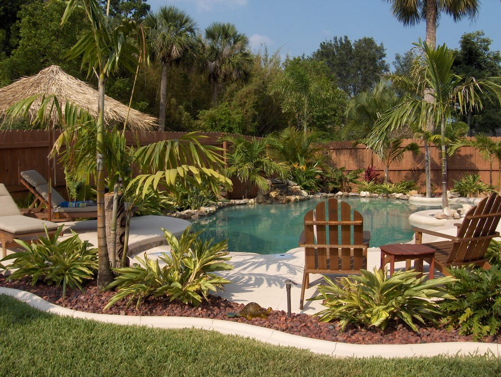 A tropical swimming pool with a boulder water feature along with wooden outdoor chairs and beige lounge chairs paired with a tiki hut umbrella.