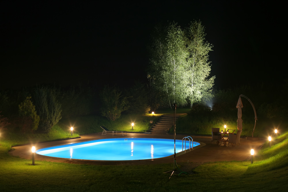 A luminous swimming pool stands out on this place surrounded with plants and illuminated by garden lights. It includes a sitting area and lounge chair next to it.