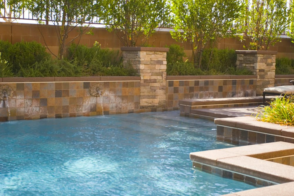 A closeup look at this swimming pool featuring decorative water spouts fixed to the retaining wall that's clad in brown mosaic tiles.