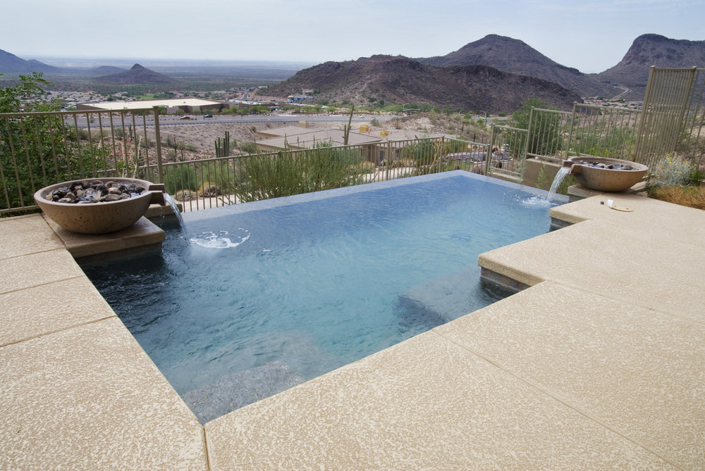 An infinity pool framed with metal fences showcases a pair of water features coming out from the bowls that are filled with stones.