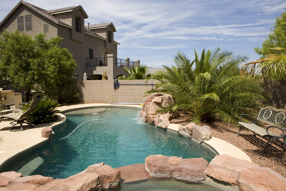 A swimming pool with boulder waterfall along with cozy loungers and a wooden bench that sits on the pebbled garden.