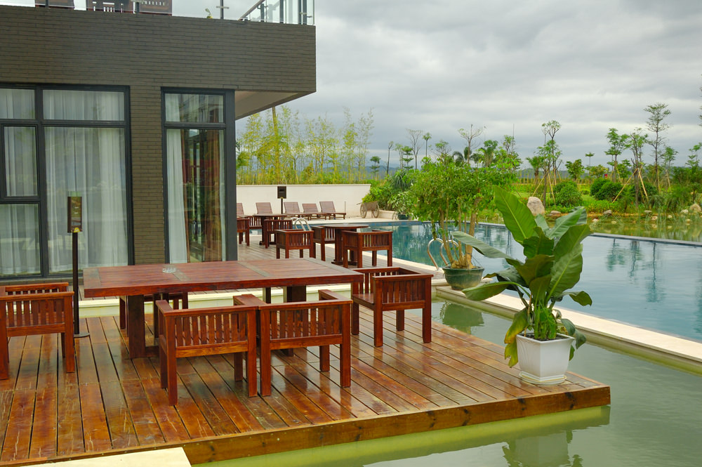 A glazed house with a wooden deck that matches with the wood plank tables and chairs beside the swimming pool with stainless steel handrails.
