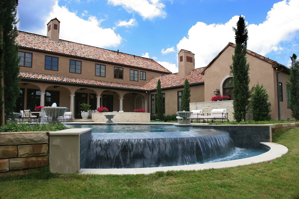 This house features a luxury swimming pool with a fancy waterfall on its edge. It is accented with fountains, lovely flowers and pine trees that create a serene ambiance to this place.