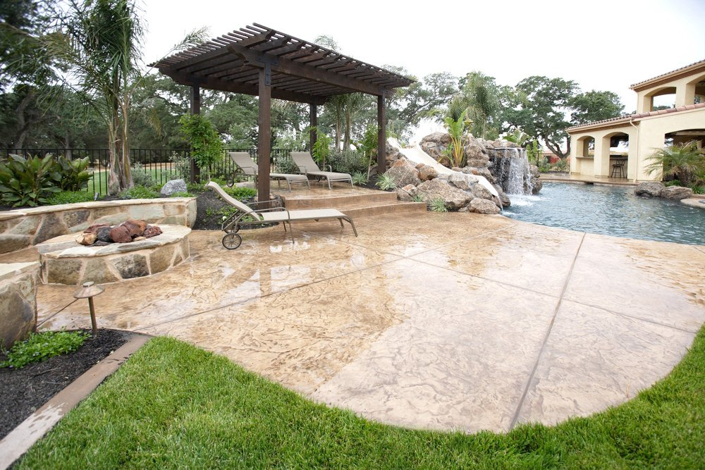 A gorgeous swimming pool boasts a waterfall and a  slide next to the rustic pergola with mobile lounge chairs. It also includes a fire pit over concrete paver.