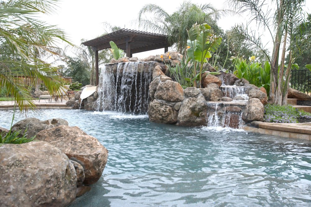 A closeup look at this swimming pool boasting a boulder waterfall along with a waterslide that's placed next to the rustic pergola.