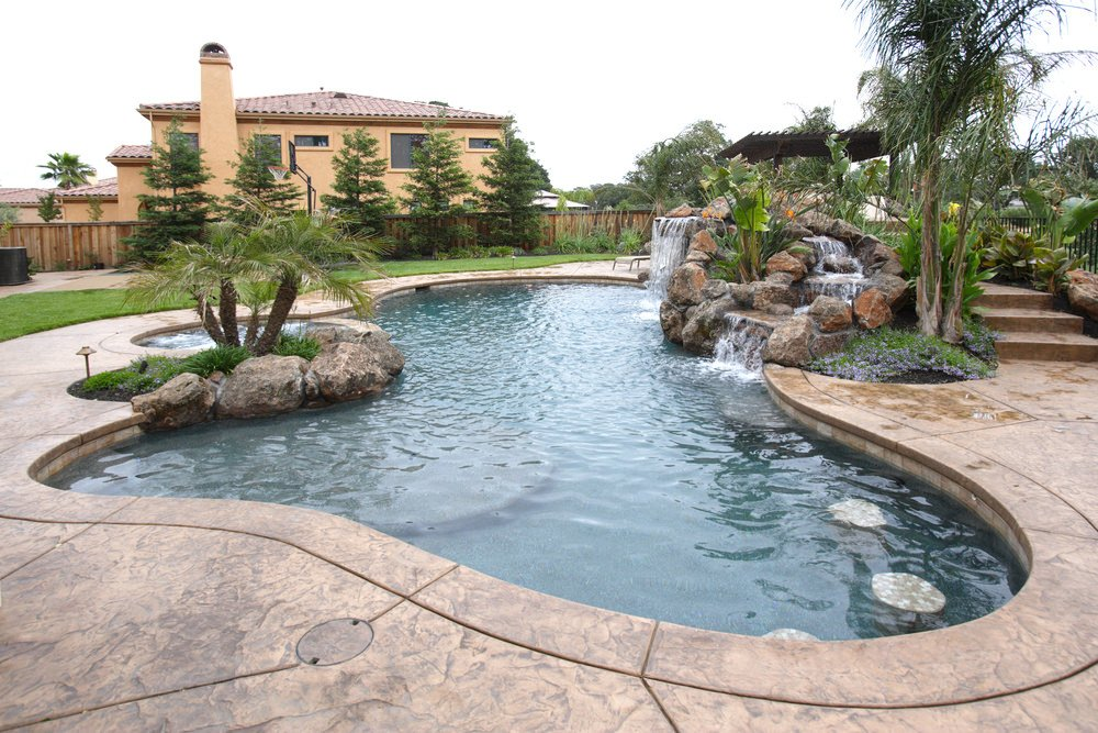 The whole look of this swimming pool showing the boulder waterfall and a jacuzzi on the other side situated behind the large stones with palm trees and plants.